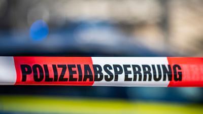"""Ein Absperrband mit der Aufschrift """"Polizeiabsperrung"""" ist vor einem Polizeiwagen aufgespannt."""