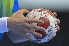 Ein Handballspieler hält den Spielball in den Händen.