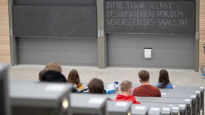 Studierende mit Mund- und Nasenmaske sitzen in einem Hörsaal.