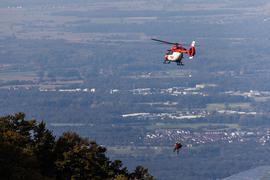Einsatzkräfte der DRF Luftrettung sowie der Bergwacht hängen von einem Rettungshubschrauber am Seil.