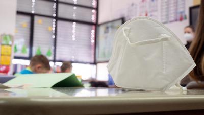 Eine FFP2-Maske liegt in einer Grundschule auf einem Tisch.
