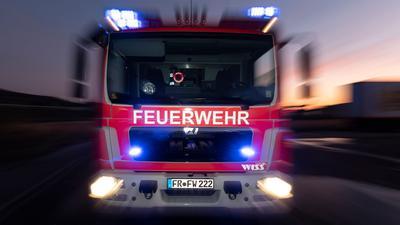 Ein Feuerwehrfahrzeug steht mit eingeschaltetem Blaulicht auf einer Straße.