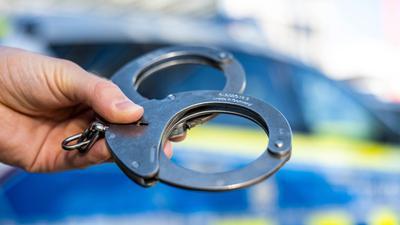 Eine Hand hält Handschellen vor einen Streifenwagen der Polizei.