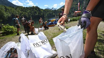 Eine Gruppe von Freiwilligen sammelt Müll am Ufer des Freibergsees.