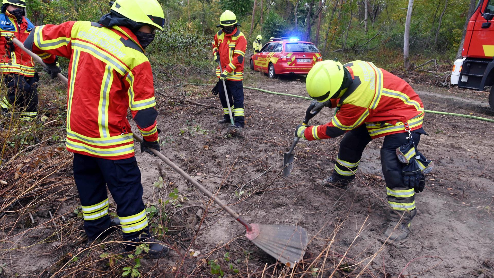 Angehörige der freiwilligen Feuerwehr Graben-Neudorf demonstrieren in einem Wald bei Bruchsal wie eine Brandschneise im Boden erstellt wird . Anlass war eine Pressekonferenz, bei der über die Modellregion integriertes Waldbrandmanagement informiert wurde.