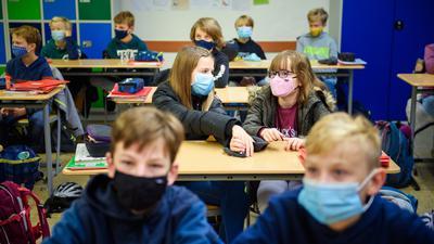 Schüler einer sechsten Klasse sitzen während des ersten Unterrichts in ihrem Klassenzimmer und tragen dabei eine Alltagsmaske.