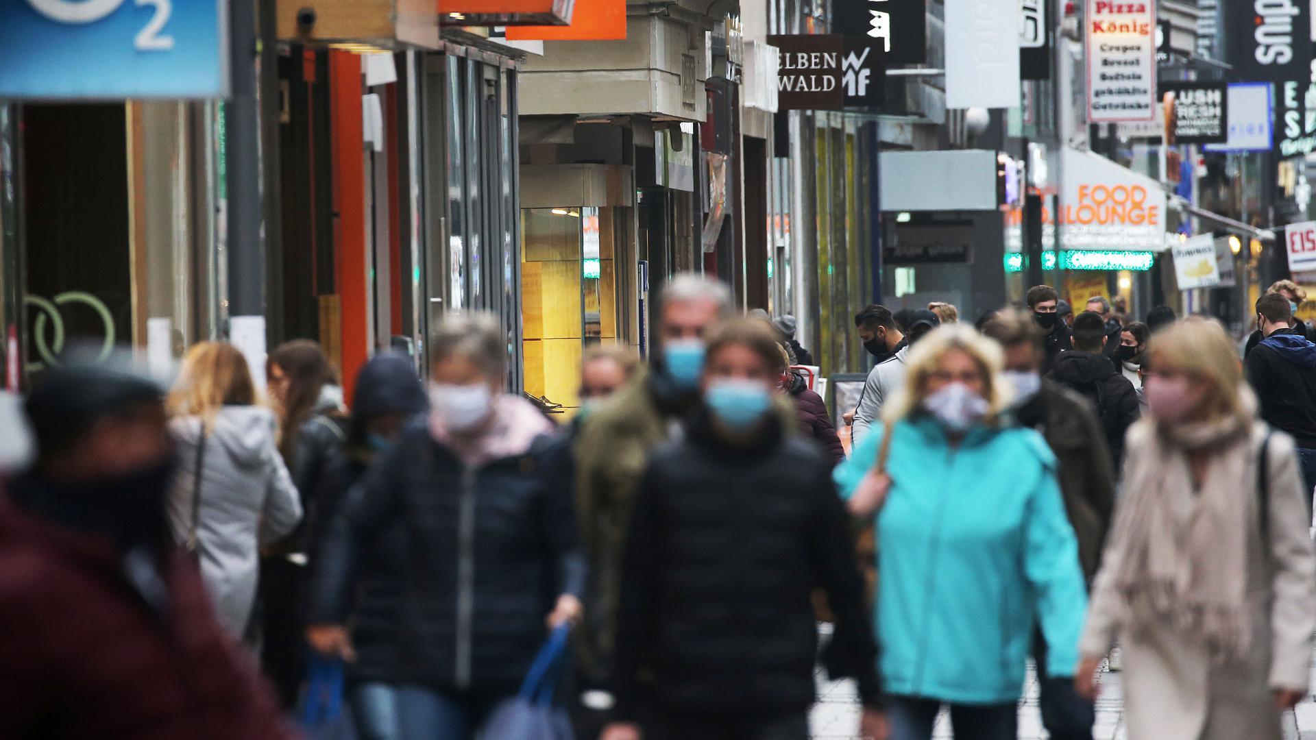 19.10.2020, Nordrhein-Westfalen, Köln: Menschen gehen mit Schutzmasken durch die Fußgängerzone. Angesichts steigender Infektionszahlen hatte das Landeskabinett am vergangenen Freitag schärfere Regeln beschlossen. Foto: Oliver Berg/dpa +++ dpa-Bildfunk +++