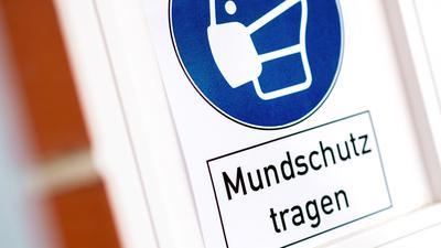"""Ein Schild mit der Aufschrift """"Mundschutz tragen"""" hängt am Eingang einer Kirche in Hannover."""