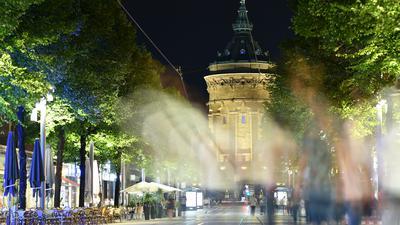 Menschen gehen am späten Abend in der Fußgängerzone der Mannheimer Innenstadt vor dem Wasserturm.