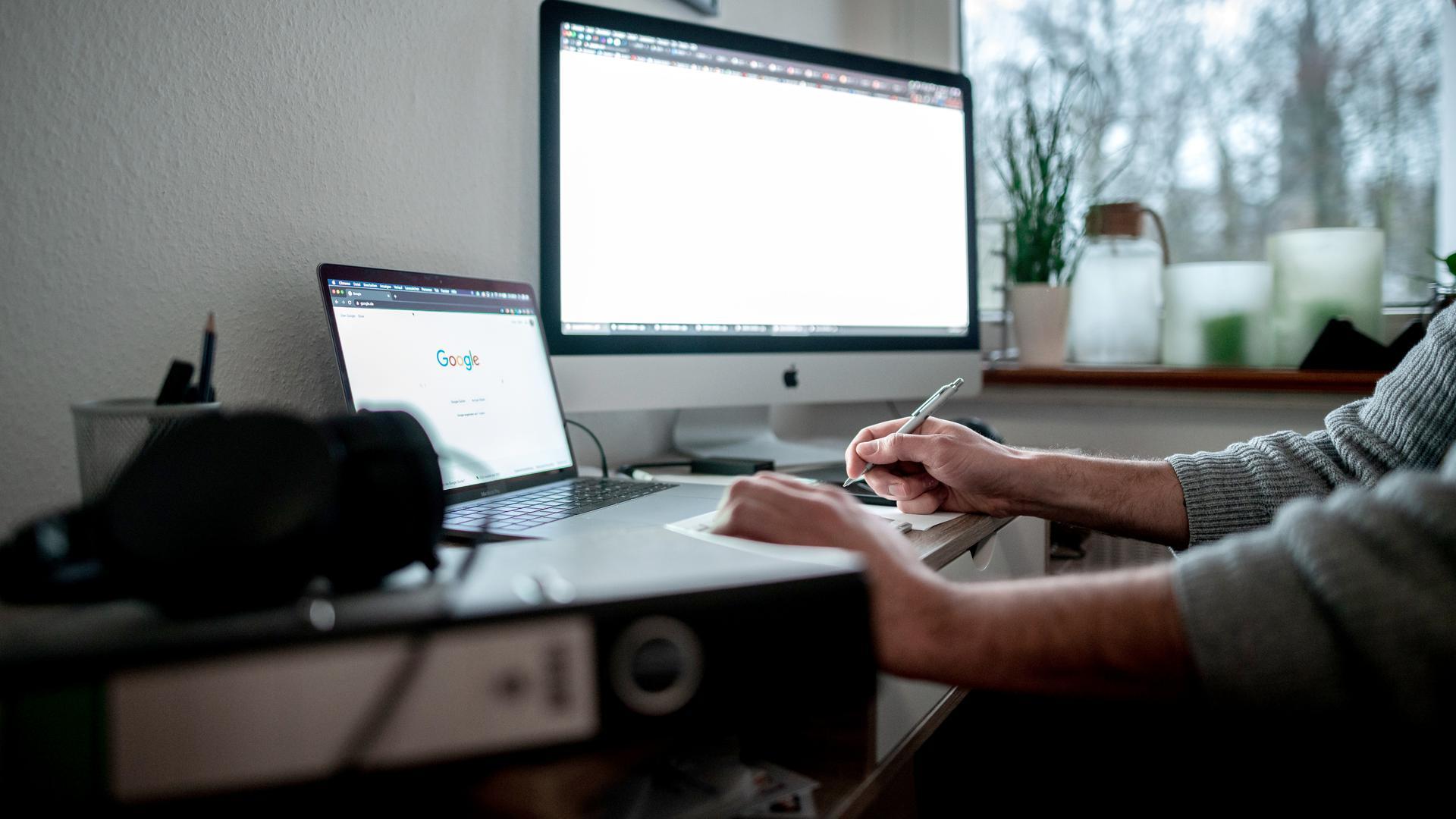 Ein Mann sitzt mit einem Laptop und einem Bildschirm an einem Tisch vor einem Fenster im Homeoffice.