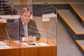NRW-Ministerpräsident Armin Laschet sitzt im Plenum des Düsseldorfer Landtags in einer Plexiglas-Box.
