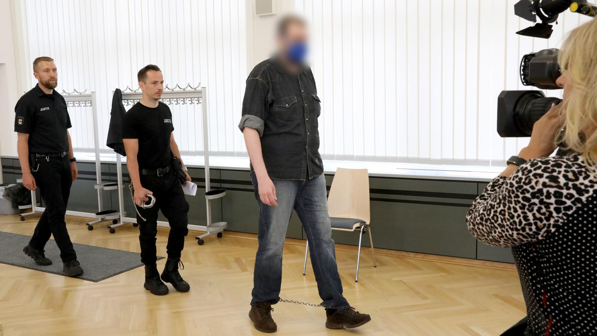 Justizmitarbeiter führen den 39-Jährigen in den Saal des Rostocker Landgerichts.