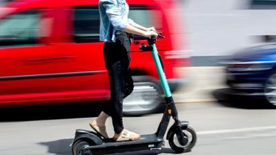Eine junge Frau unterwegs mit einem E-Scooter in Hannover.