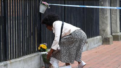 EineFrau legt zum Gedenken an die Opfer im Stadtzentrum von Reading Blumen nieder.