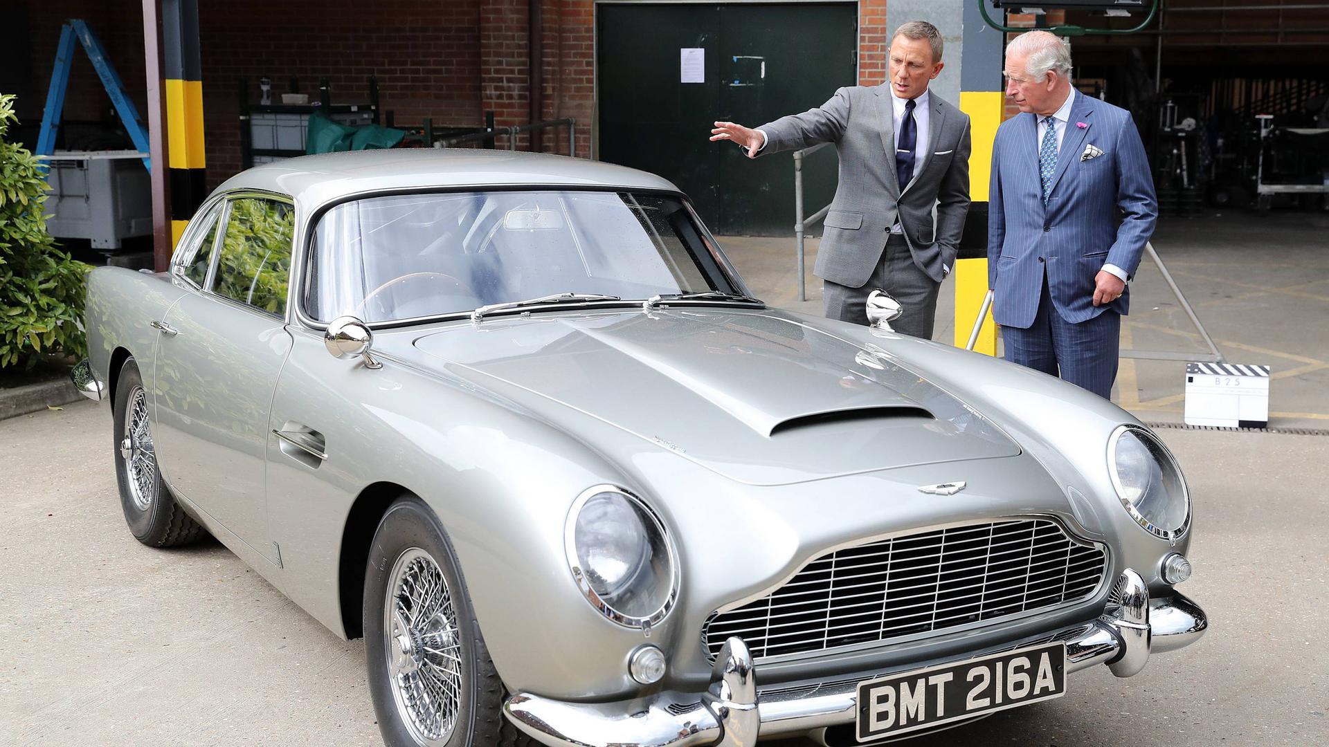 20.06.2019, Großbritannien, Iver Heath: Charles (r), britischer Prinz von Wales, steht mit dem Schauspieler Daniel Craig bei einem Besuch des Sets des 25. James-Bond-Films in den Pinewood Studios hinter dem Aston Martin DB5 Bond-Auto aus einem Bond-Film, während Craig spricht. Foto: Chris Jackson/PA Wire/dpa +++ dpa-Bildfunk +++ |