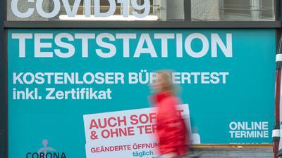 25.08.2021, Bayern, München: Eine Person geht im Stadtteil Schwabing an einer Covid-19 Teststation vorbei, die auch kostenlose Bürgertest inklusiv Zertifikat und ohne Termin anbietet. Foto: Peter Kneffel/dpa +++ dpa-Bildfunk +++