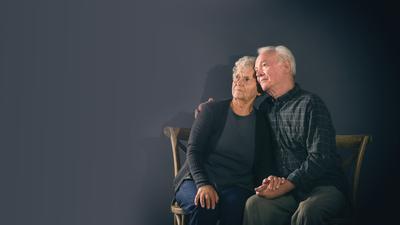 Poor pensive elderly couple on dark background