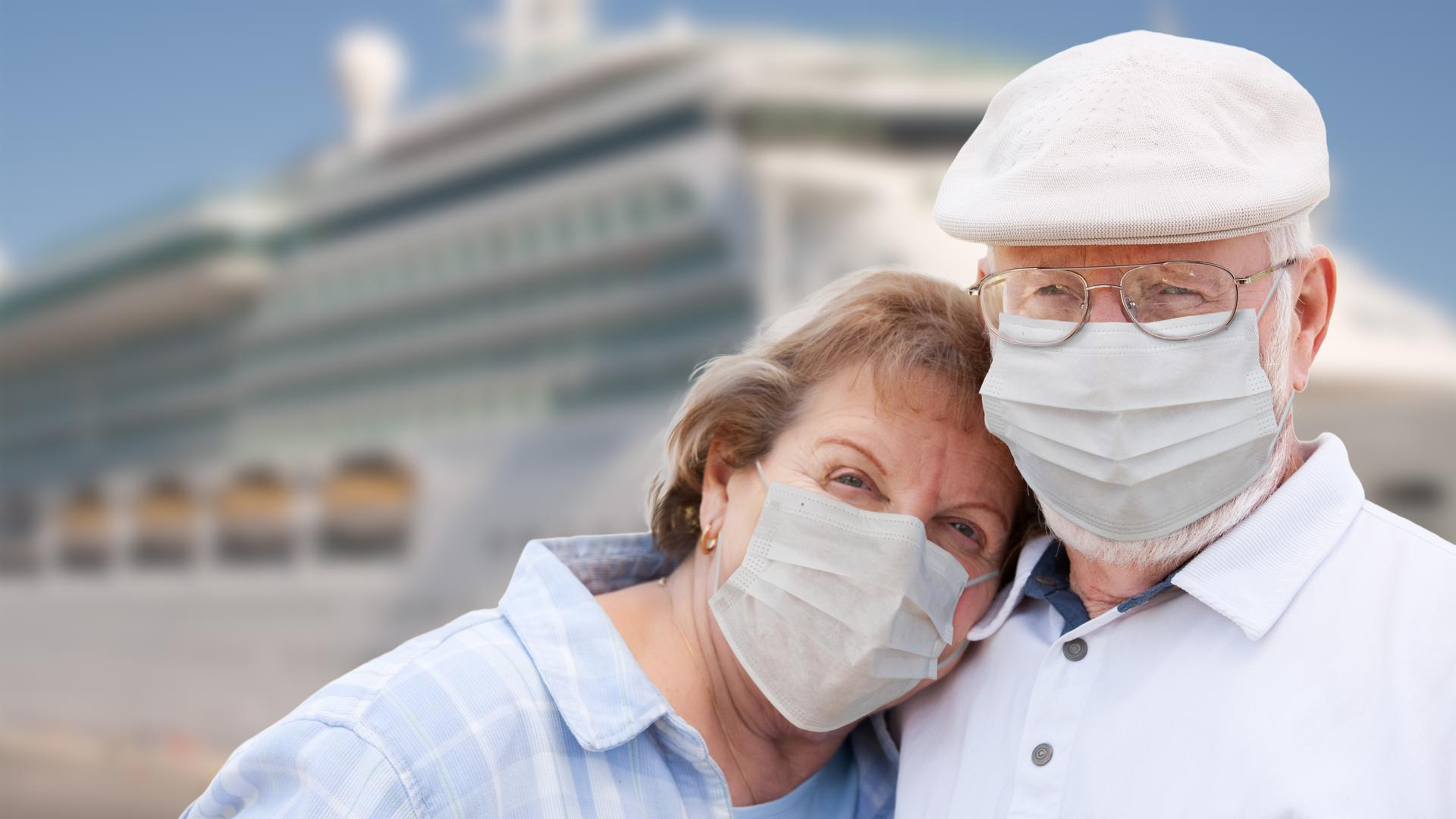Senior Couple Wearing Face Masks Standing In Front of Passenger Cruise Ship.
