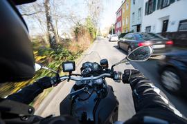 Ein Motorradfahrer fährt durch eine Wohngegend.