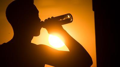 Ein junger Mann sitzt auf dem Kronsberg, und trinkt Bier, während am Horizont die Sonne untergeht.