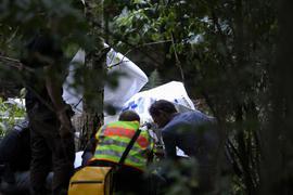 Einsatzkräfte der Polizei stehen am Wrack eines der abgestürzten Ultraleichtflugzeuge.