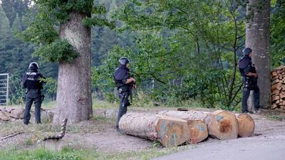 Polizisten stehen vor einem Waldstück an einer Straße bei Oppenau. Am Vortag hatte ein Mann bei einer Kontrolle Polizisten bedroht und entwaffnet.