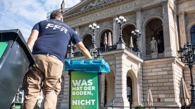 Am Morgen nach den Krawallen stellt ein Mitarbeiter der Stadtreinigung vor der Alten Oper geleerte Mülltonnen auf.