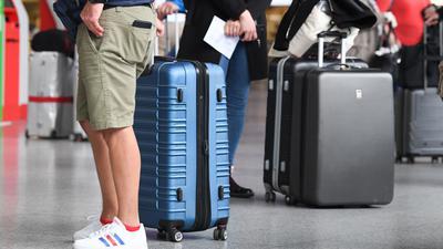 Flugreisende stehen in Terminal 1 des Frankfurter Flughafens am Check-in-Schalter an. Reiserückkehrer aus Risikogebieten sollen sich an Flughäfen verpflichtend auf das Coronavirus testen lassen.