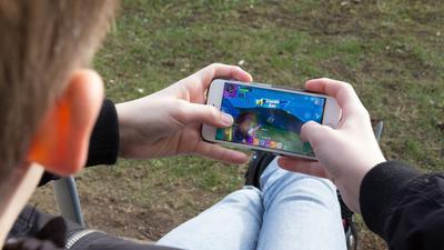 """Ein Junge spielt auf seinem Mobiltelefon. """"Unsere Studie zeigt, dass wir dringend ein verlässliches und umfassendes Frühwarnsystem gegen Mediensucht brauchen"""", sagt DAK-Vorstandschef Andreas Storm."""