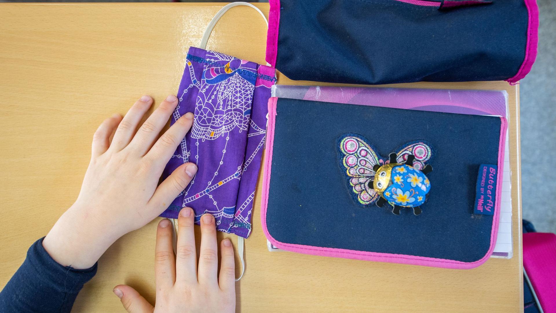 Eine Schülerin einer Grundschulklasse legt ihren Mundschutz neben ihre Schulmappe.