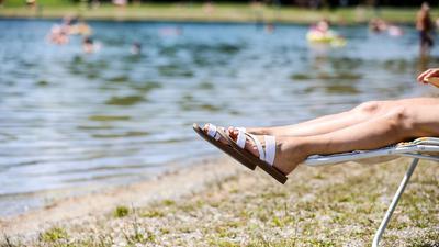 Eine Frau liegt bei sommerlichen Temperaturen an einem Badesee.