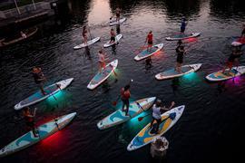 Teilnehmer einer Ausflugsgruppe fahren mit leuchtenden LED-Stand-Up-Paddles in den Abendstunden über einen Alsterfleet in Hamburg.