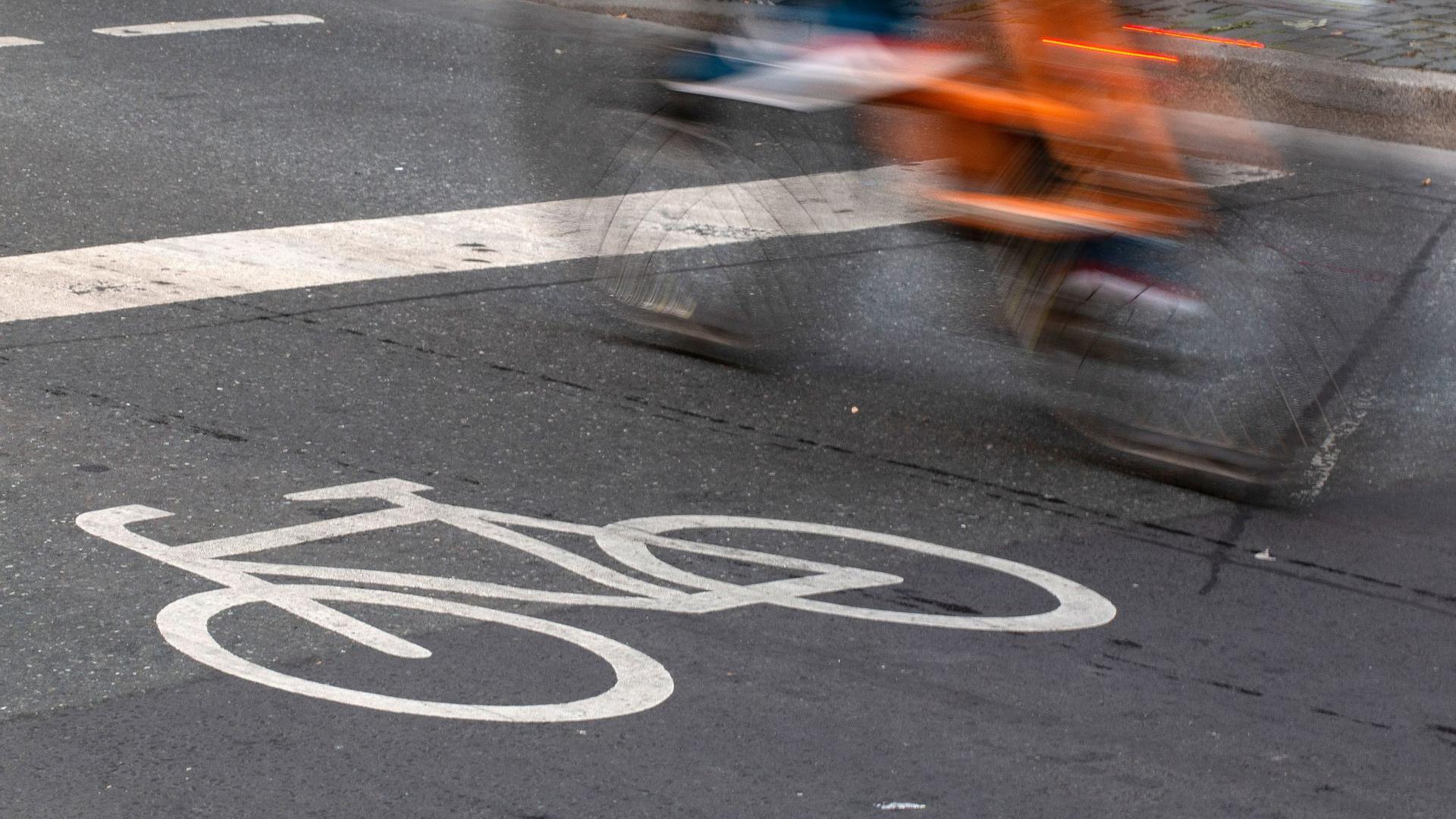 Ein Fahrradfahrer fährt in der Innenstadt über einen Radweg.