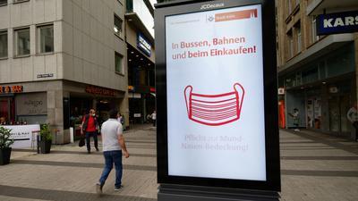 Ein Werbebildschirm weist in der Kölner Innenstadt auf die Maskenpflicht in Geschäften und im Nahverkehr hin.