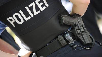 Eine Polizistin trägt ihre Dienstwaffe am Gürtel.