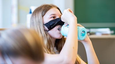 Eine Schülerin der Klasse 8a der Gesamtschule in Münster hebt ihre Mund- und Nasenmaske an, um etwas zu trinken.