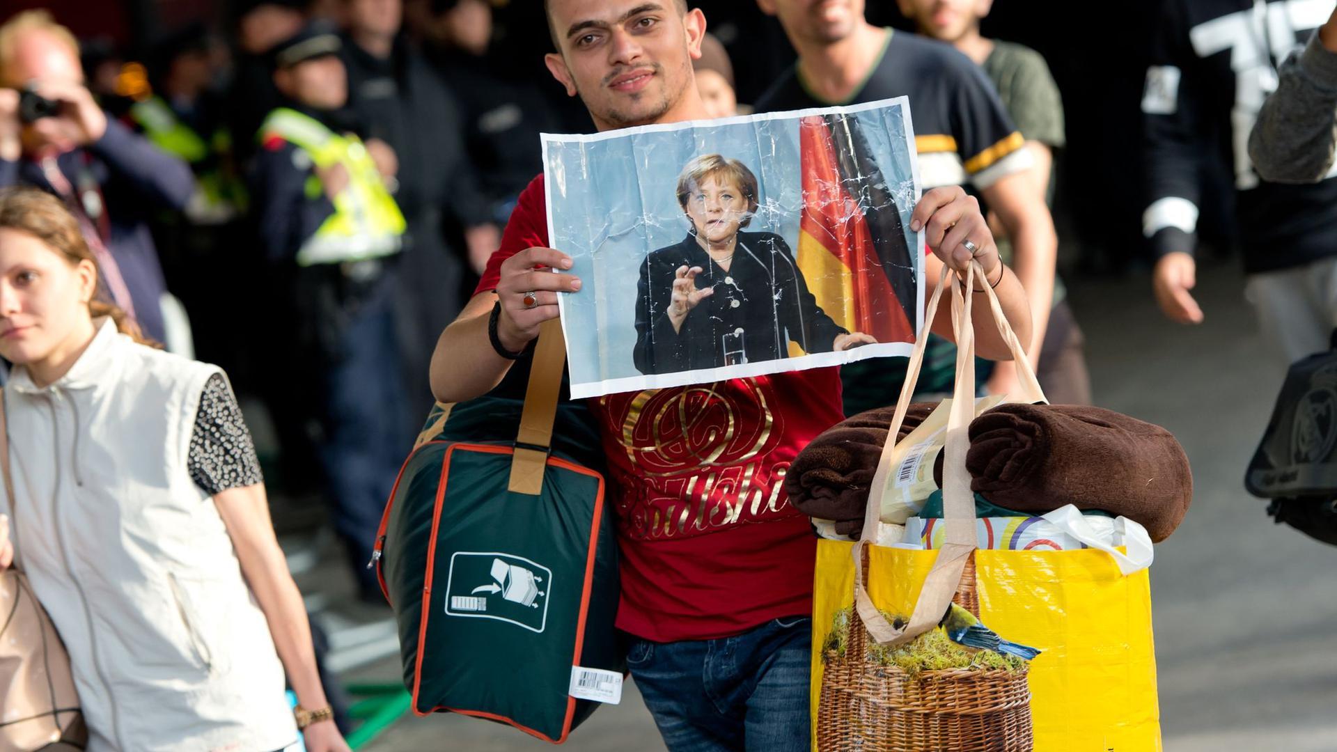 Ein Flüchtling, der kurz zuvor mit einem Zug angekommen ist, hält voller Hoffnung ein Foto von Angela Merkel in den Händen.(Archiv)