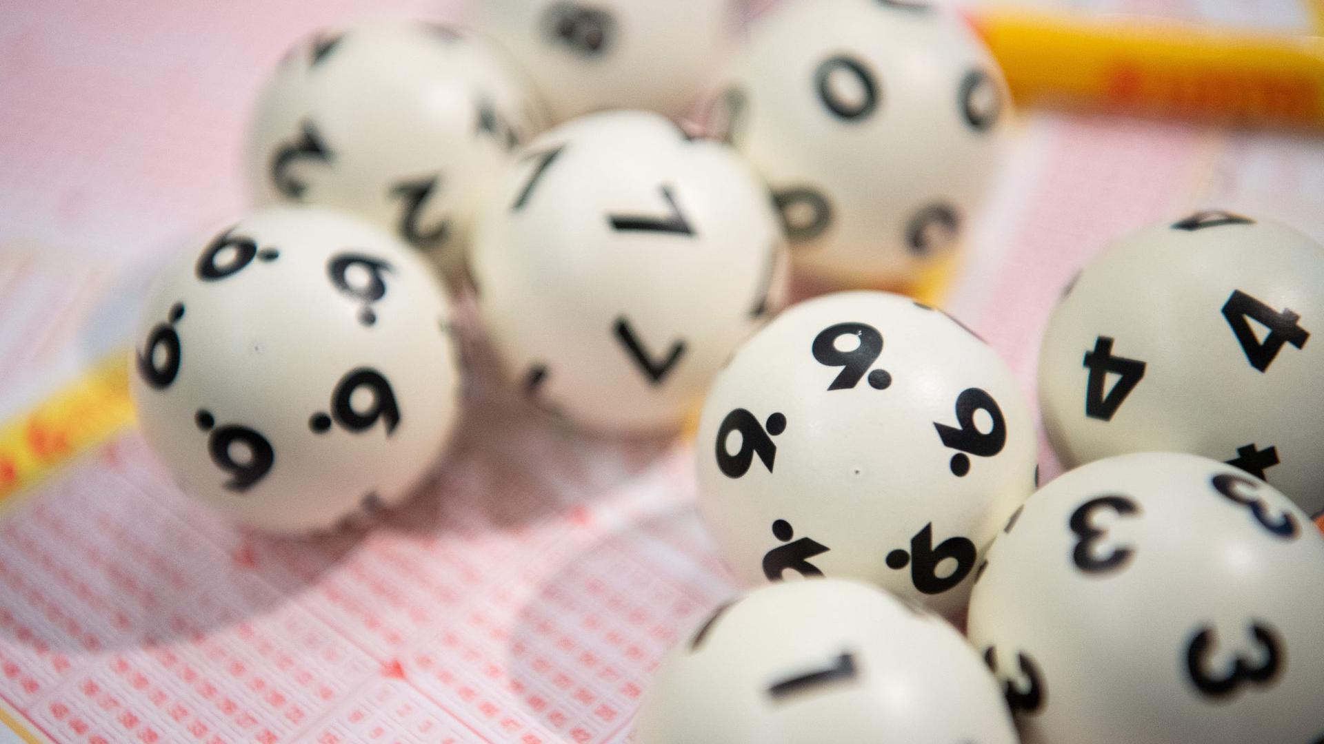 Lottokugeln liegen auf einem Lottoschein.