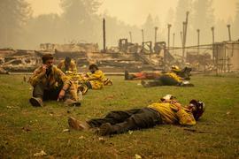 Eine Feuerwehrmannschaft macht eine Pause neben einer Schule in Berry Creek in Nordkalifornien, die durch ein Feuer zerstört wurde. Verheerende Waldbrände wüten weiter entlang weiten Teilen der US-Westküste.