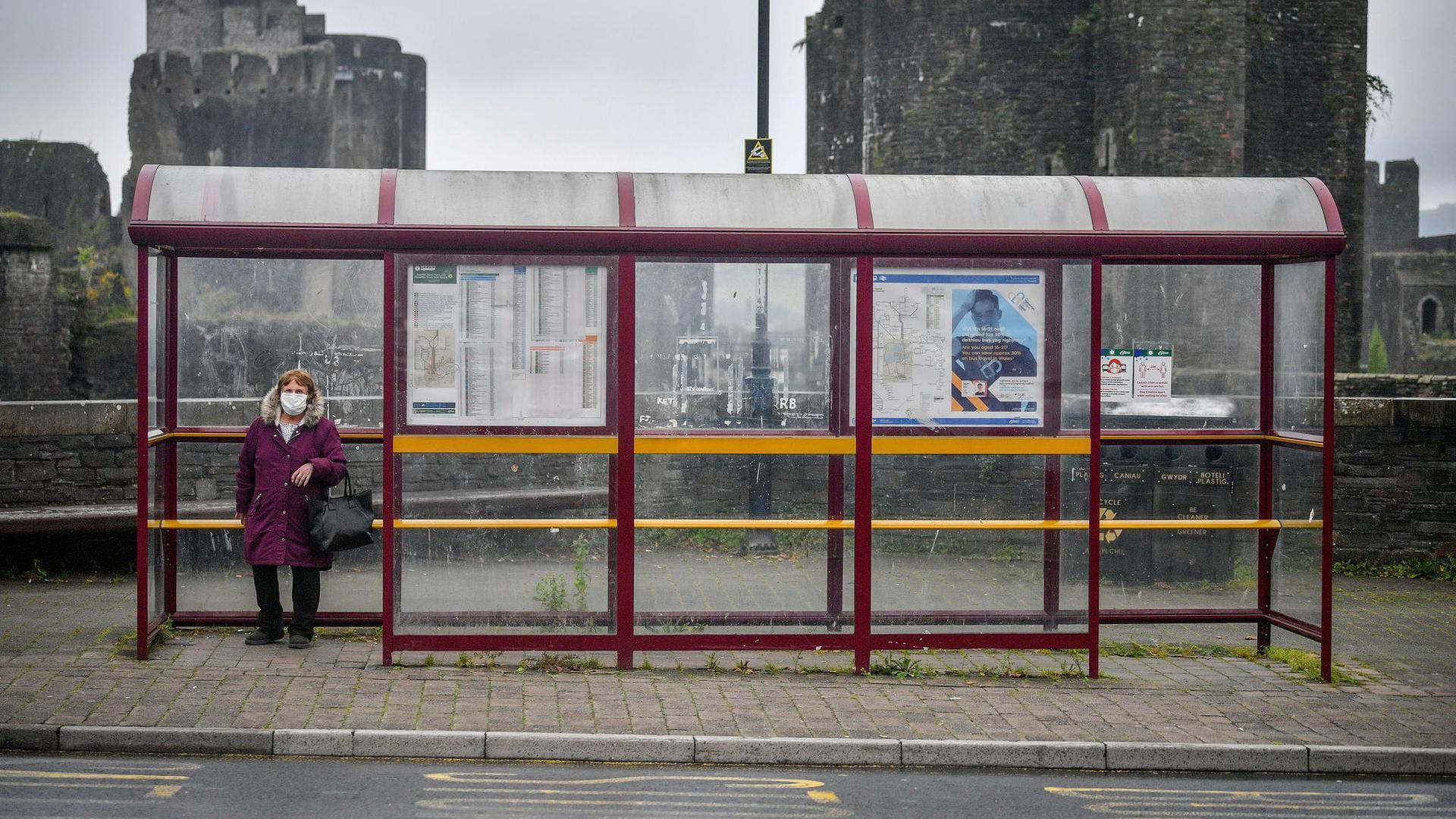Eine Frau mit Mundschutz wartet in Caerphilly an einer Haltestelle auf den Bus. Medienberichtenn zufolge plant die Regierung inLondon einen erneutenlockdown vor.