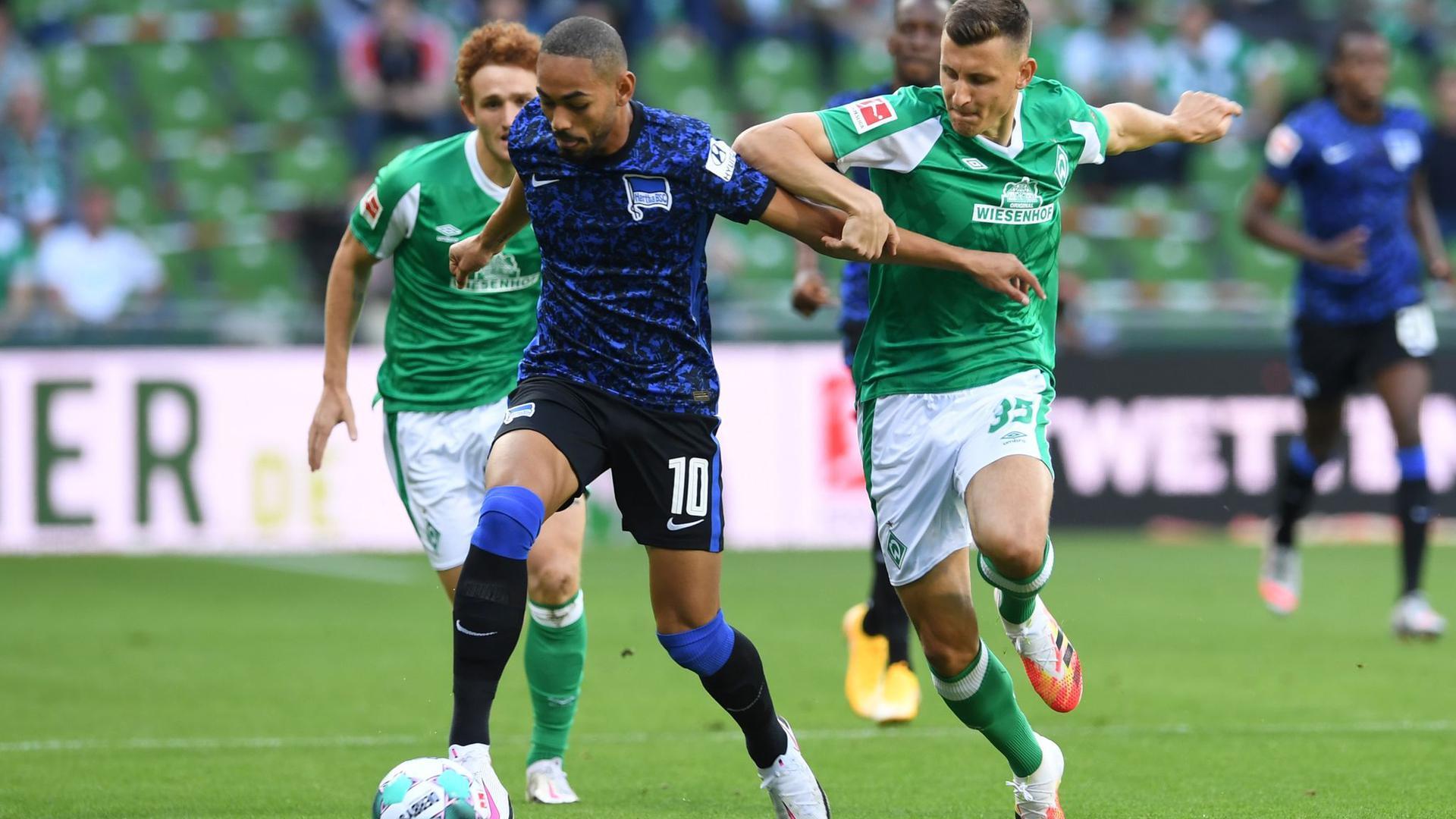Josh Sargent (l) und Maximilian Eggestein (r) von Werder Bremen versuchen Herthas Matheus Cunha zu stoppen.