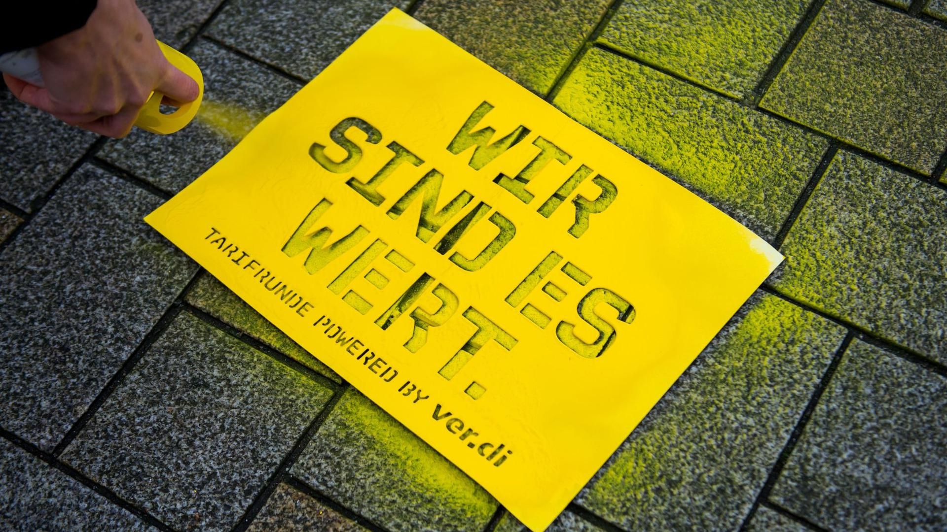 """Eine Teilnehmerin eines Warnstreiks der Tarifbeschäftigten sprüht den Schriftzug """"Wir sind es Wert"""" auf den Boden."""