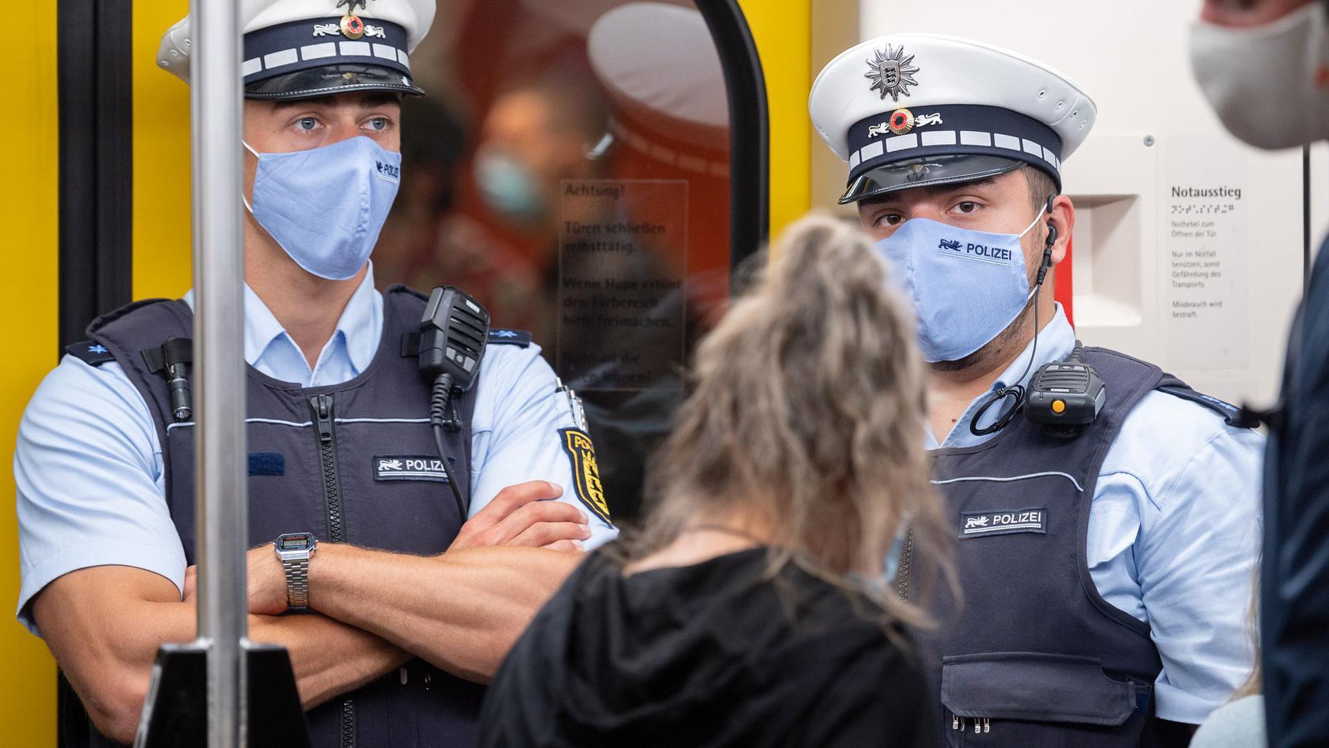 Polizeibeamte kontrollieren in einer Stuttgarter U-Bahn die Einhaltung der Maskenpflicht.