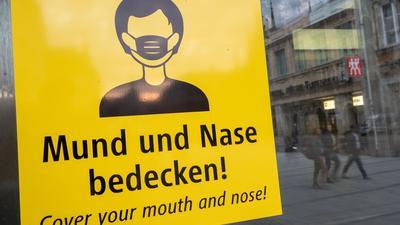Auf dem Münchener Marienplatz fordert ein Schild zum Tragen eine Mund-Nasen-Bedeckung auf.