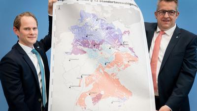 Stefan Studt (r.), BGE-Vorsitzender und Steffen Kanitz, Mitglied der Geschäftsführung der BGE, zeigen eine Landkarte mit Teilgebieten für die Endlagersuche.