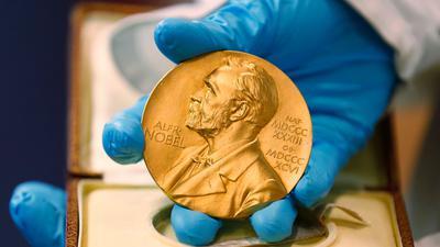 Ein Mitarbeiter der Nationalbibliothek zeigt eine goldene Nobelpreismedaille.