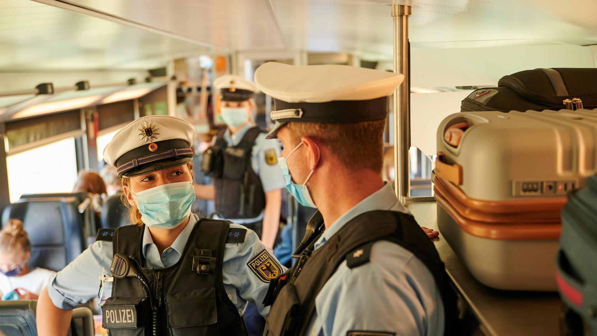 Beamte der Bundespolizei und Mitarbeiter der DB Sicherheit kontrollieren in einem ICb die coronabedingte Maskenpflicht.