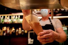 Ein Wirt mit Maske zapft in einer Kneipe im Berliner Bezirk Wilmersdorf ein Bier. Die Sperrfrist in der Bundeshauptstadt ist vor Gericht gekippt worden.