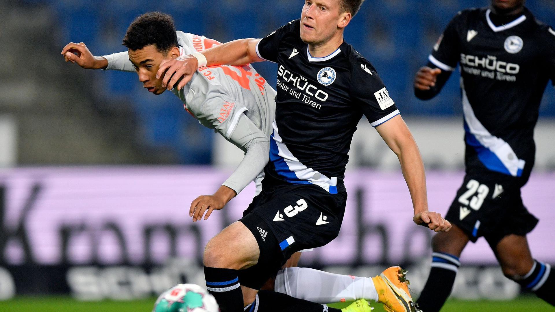Jamal Musiala (l) von Bayern in Aktion gegen Brian Behrendt (M) von Bielefeld.