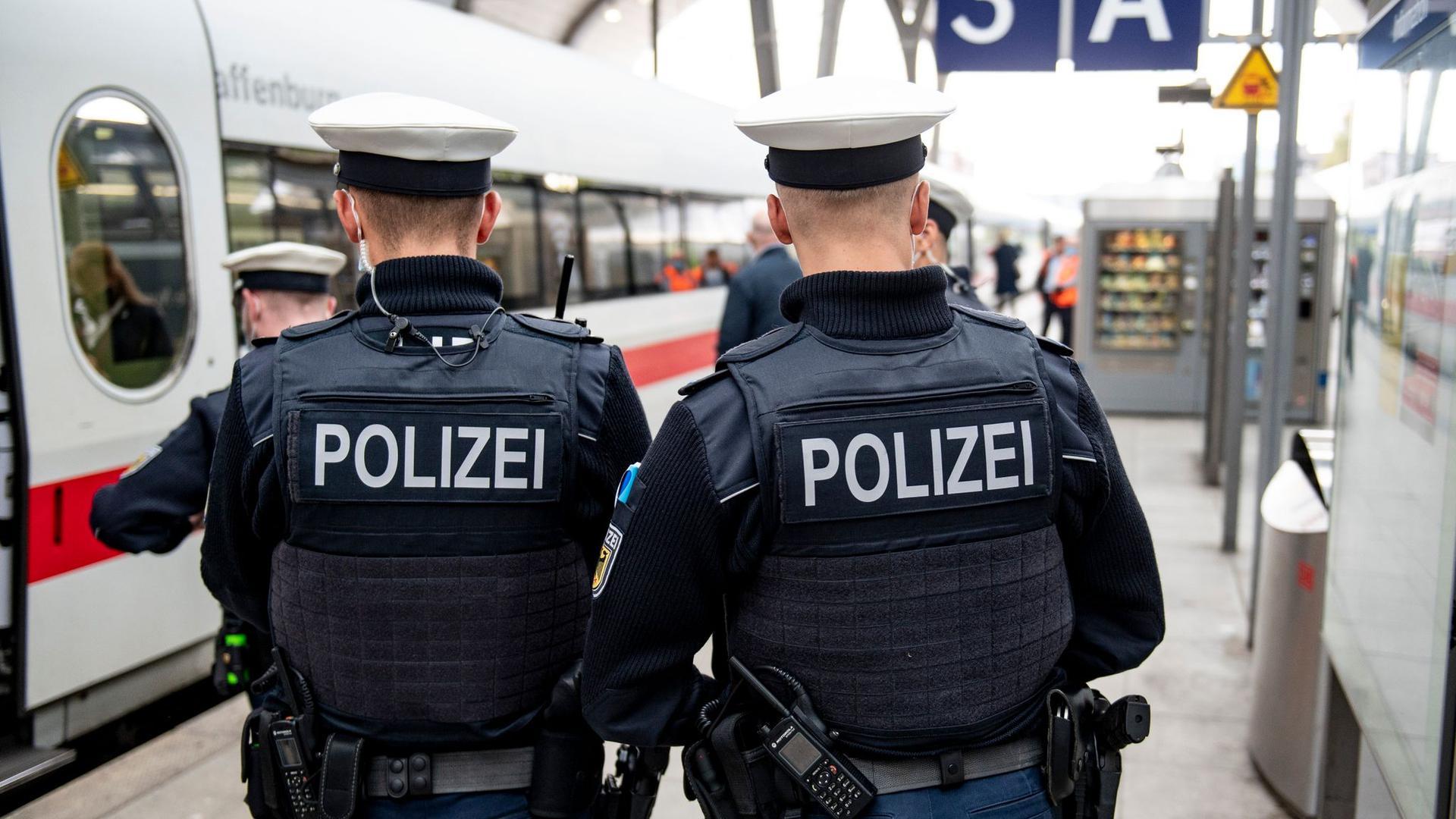 Bundespolizisten stehen vor der Abfahrt eines ICE an einem Gleis im Kieler Hauptbahnhof. In den Zügen der Deutschen Bahn wird die Mund-Nase-Bedeckungspflicht kontrolliert.